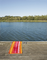 Towel and flip-flops by lake