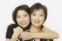 Studio shot of Asian mother and adult daughter hugging