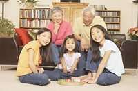 Three young Asian sisters playing chinese checkers while grandparents watch,San Rafael,California,United States