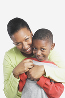 Studio shot of African mother hugging her young son,San Rafael,California,United States