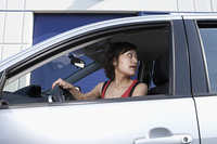 Asian woman looking over shoulder in car