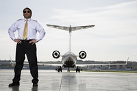 Asian male pilot with airplane in background
