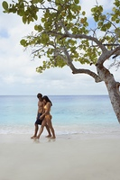 South American couple walking on beach