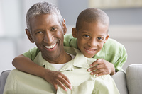 African American grandfather and grandson hugging
