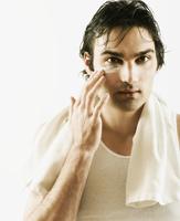 European man applying facial treatment