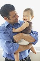Hispanic father holding daughter