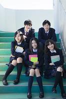踊り場で座る高校生たち