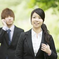新緑の中で微笑むビジネスウーマンとビジネスマン