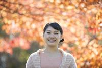 紅葉の前で微笑む女性