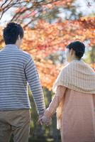 紅葉の前で手をつなぐカップルの後姿