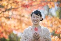 紅葉を持ち微笑む女性