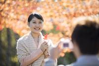 紅葉の前で写真を撮るカップル