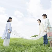 草原でシートを広げる3人の女性