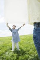 草原でシートを広げる女性