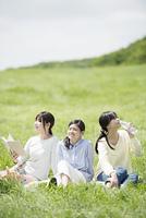 草原でピクニックをする3人の女性