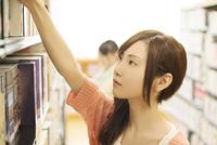 図書館で本を選ぶ女性