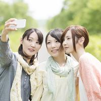 スマートフォンで自分撮りをする大学生