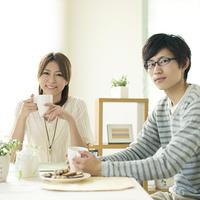 コーヒーを飲みながら微笑むカップル