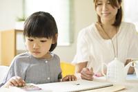 お絵描きをする女の子と母親