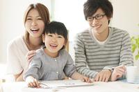お絵描きをする女の子と両親