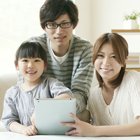 タブレットPCを持ち微笑む親子