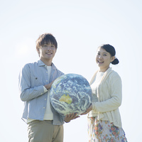 地球のボールを持ち微笑むカップル