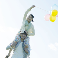 風船を持ち肩車をするカップル