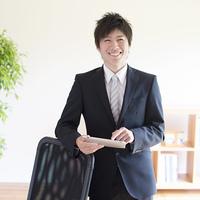 タブレットPCを持ち微笑むビジネスマン