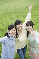 草原で微笑む3人の女性