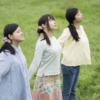草原で深呼吸をする3人の女性