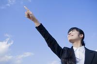 空に指を指すビジネスウーマン