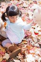 落ち葉の上で遊ぶ母と娘