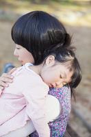 母にだっこされて眠る女の子