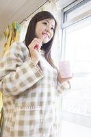 窓際で歯磨きする女性