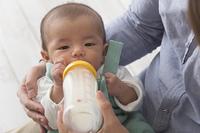 子供にミルクを飲ませる夫婦