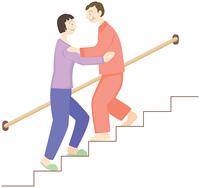 階段を下りる高齢者と介護者