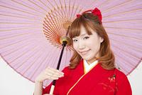 和傘を差し微笑む振袖姿の女性