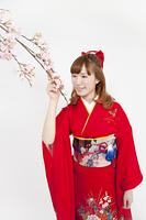 桜に触れる振袖姿の女性