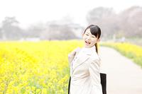 菜の花畑で微笑むOL