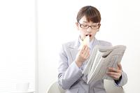 英字新聞を読みながらサンドウィッチを食べるビジネスウーマン