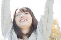 両手を上げ微笑む女性
