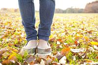 落ち葉の絨毯に立つ女性の足元