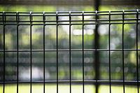 公園の針金製のフェンスの彼方に木々の暈け