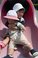 滑り台で遊ぶ姉と弟