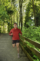 Mixed race man running in forest