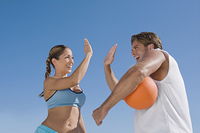 Hispanic couple with volleyball high-fiving