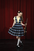 Asian girl holding violin and curtsying on stage