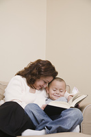Multi-ethnic grandmother and grandson reading book