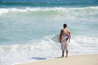 Hispanic teenager at beach with surfboard