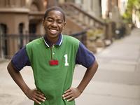 African teenage boy laughing in urban setting